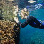 Dona practicant snorkeling i fent fotografia subaquatica a la Costa Brava